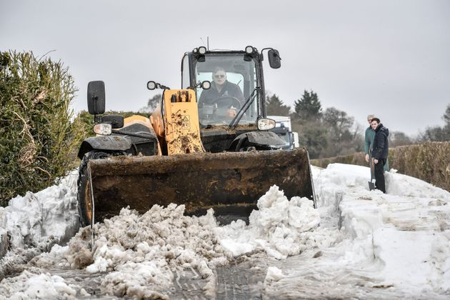 A JCB is used to scrape the road surface and clear snow after vehicles became stuck in snow near Marlborough, Wiltshire.