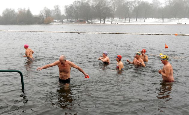 Swimmers emerge from the Serpentine lake in Hyde Park in London.