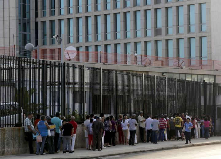 People wait to apply for visas outside the U.S. Interests Section (background) in Havana on May 22, 2015.
