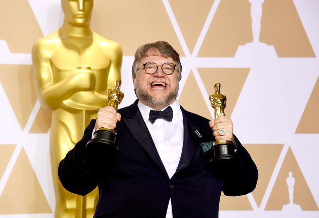 Guillermo del Toro holds his trophies for Best Picture and Best