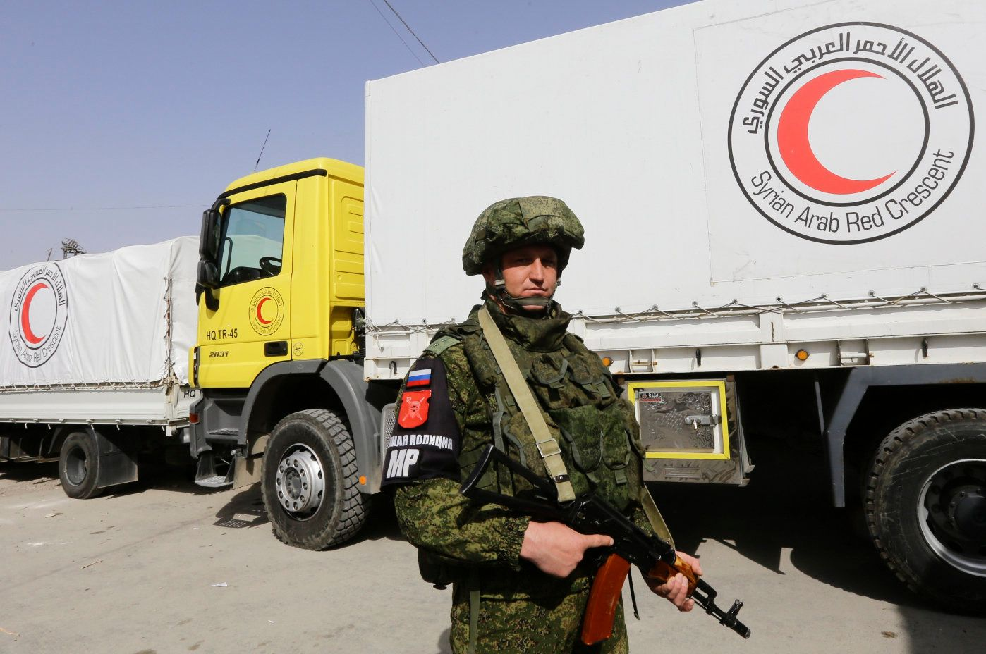 A Russian solider stands guards as Syrian Arab Red Crescent vehicles carrying aid wait at the al-Wafideen checkpoint on the outskirts of Damascus neighbouring the rebel-held Eastern Ghouta region before delivering aid to the rebel-held enclave on March 5, 2018. / AFP PHOTO / Louai Beshara        (Photo credit should read LOUAI BESHARA/AFP/Getty Images)
