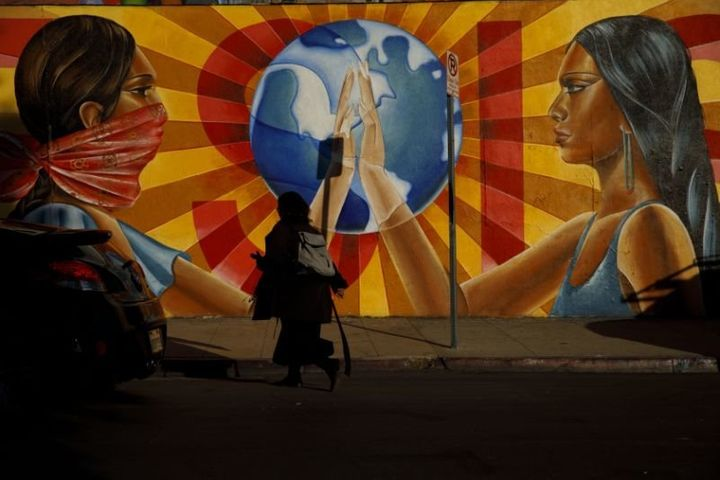 "A pedestrian walks past the mural ""¡Resiste!"" by Nanibah Chacon outside Self-Help Graphics & Art, Inc."
