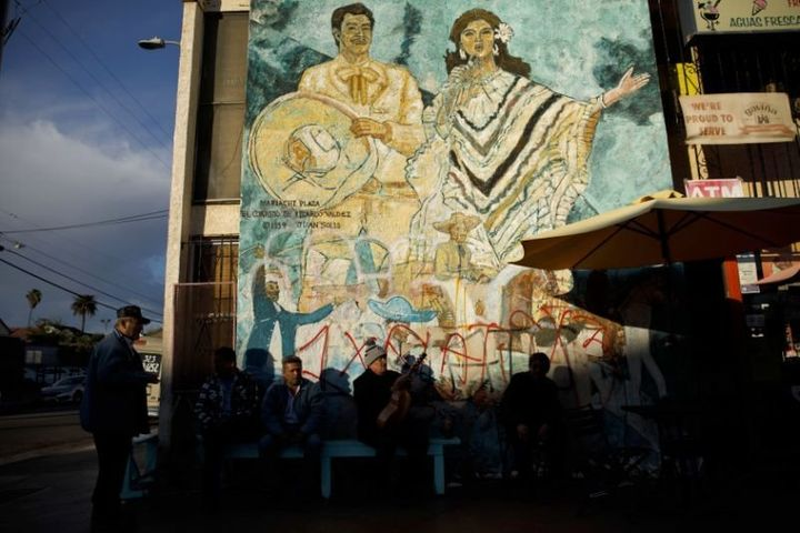 "Men sit outside a store in front of the mural ""El Corrido de Ricardo Valdez,"" painted in 1994 by Juan Solis, in M"