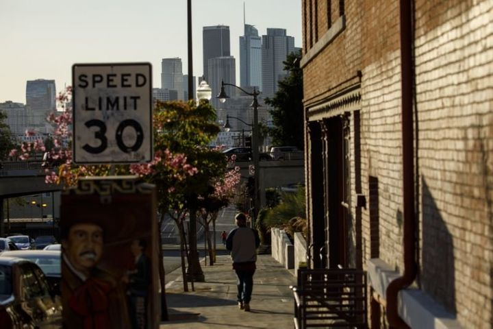 A pedestrian walks near Mariachi Plaza in Boyle Heights with the skyline of downtown Los Angeles on the horizon.