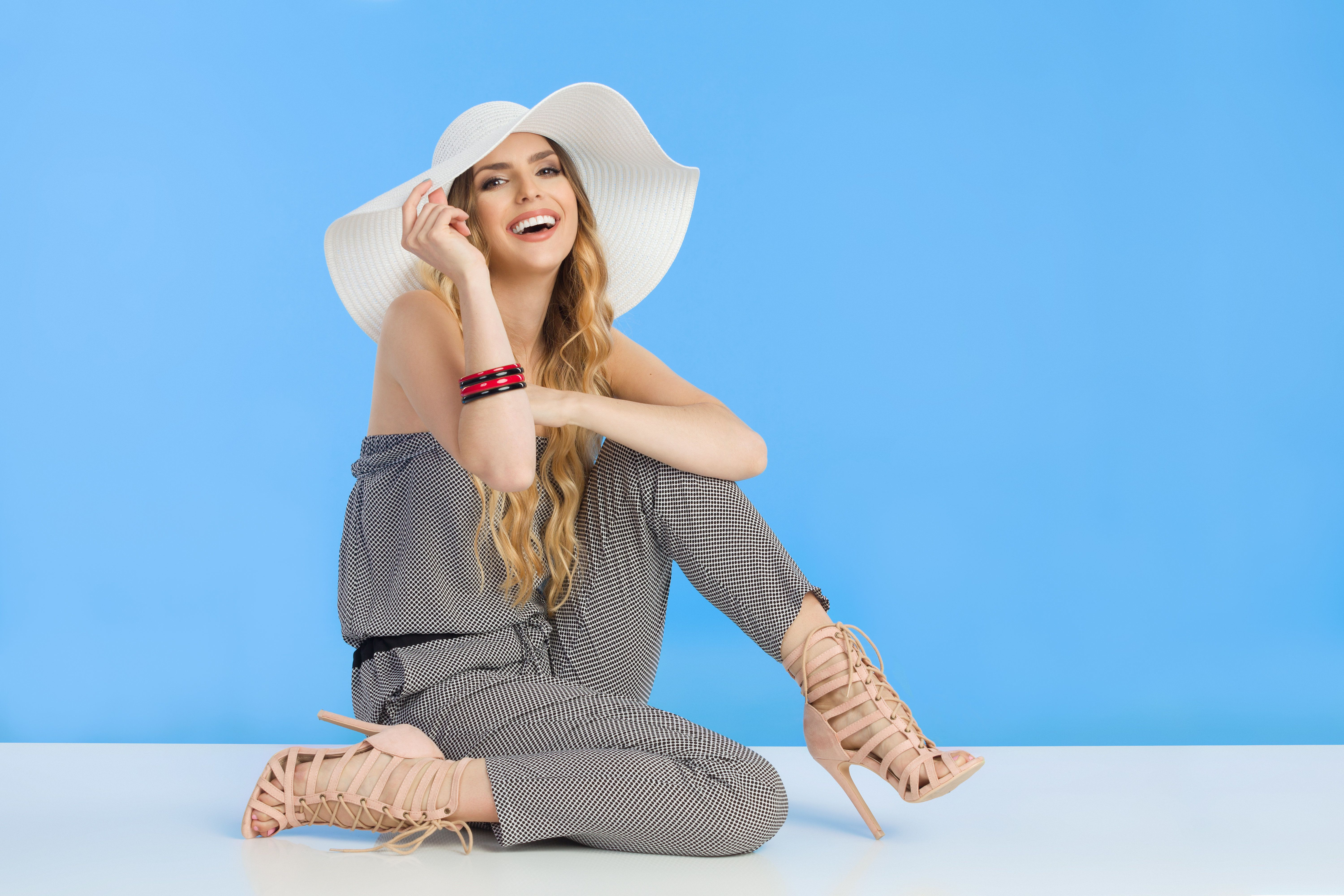 Beautiful young woman in summer jumpsuit, high heels and white sun hat is sitting on floor looking at camera and laughing. Full length studio shot.