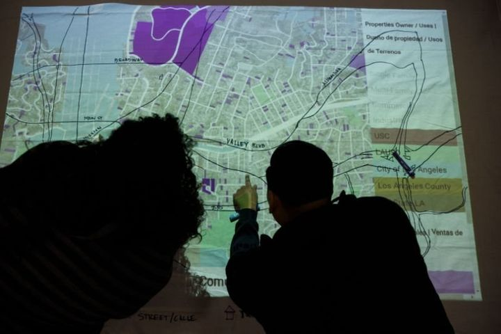 Attendees draw a community power map on a projection showing where property sales, speculation, rent increases and plans for