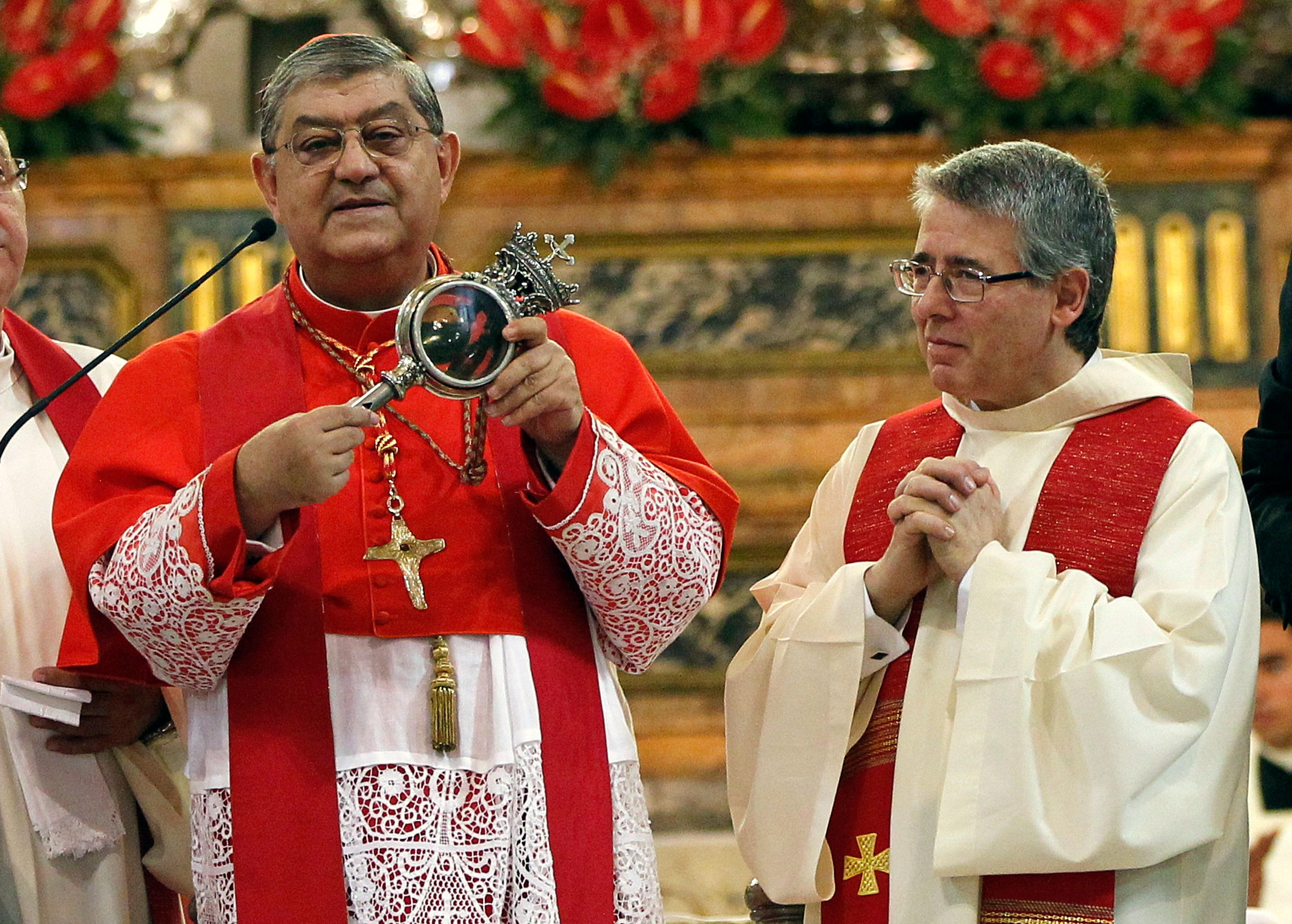 Archbishop of Naples, Cardinal Crescenzio Sepe (L) holds a flask believed to contain drops of liquefied blood of San Gennaro in Naples Cathedral, Italy, in this September 19, 2013 file photo.   REUTERS/Ciro De Luca/Files