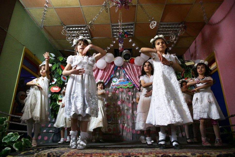 Girls dance to celebrate the end of the school year in the rebel-held besieged city of Douma, Syria, on May 22, 2017.