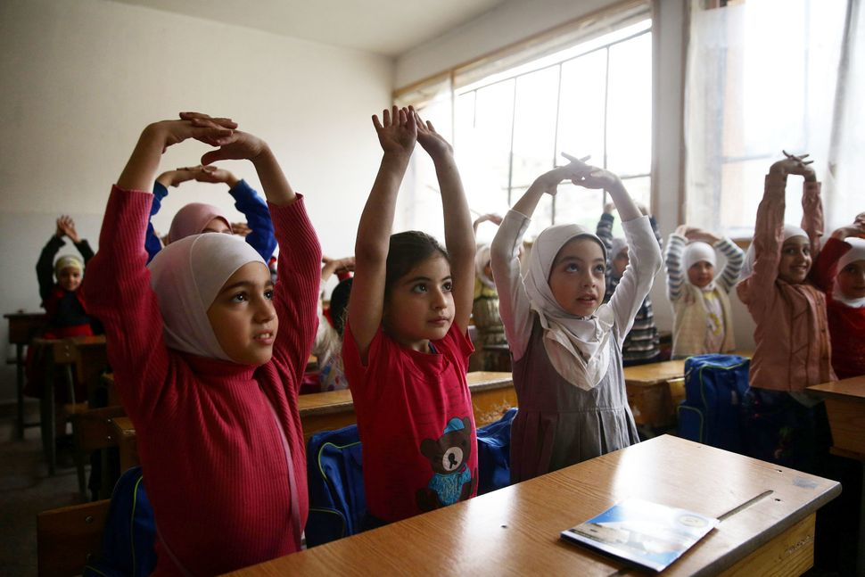 Girls attend a war safety awareness campaign, given by Civil Defense members, inside a school in the rebel-held besieged city
