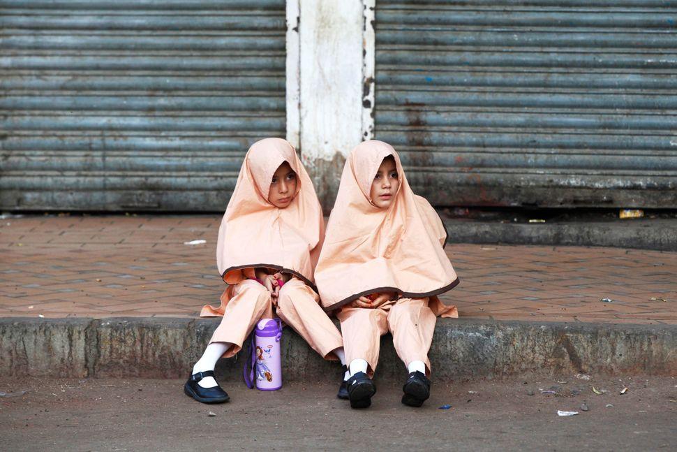 Girls in uniform sit along a sidewalk while waiting for school van in Karachi, Pakistan, on Nov. 8, 2017.