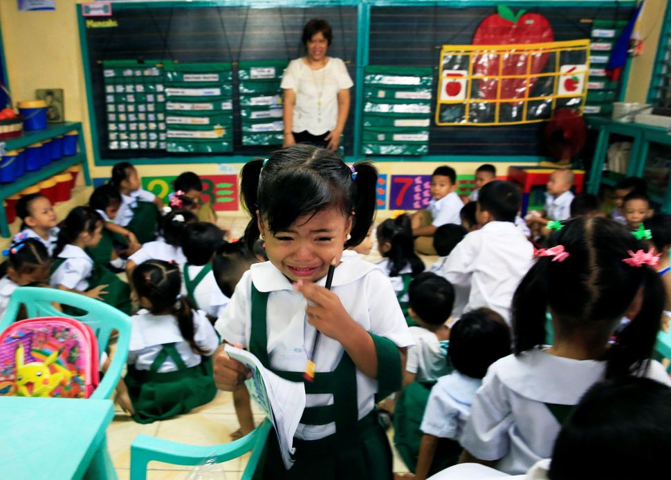 A girl cries while looking for her mother during the first day of classes at the Rosauro Almario elementary school in Manila,