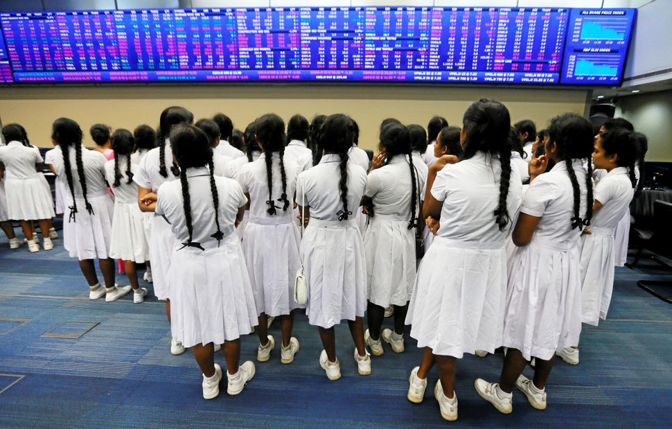 Schoolgirls stand in front of the stock display board during their visit for an education program at the Colombo Stock Market