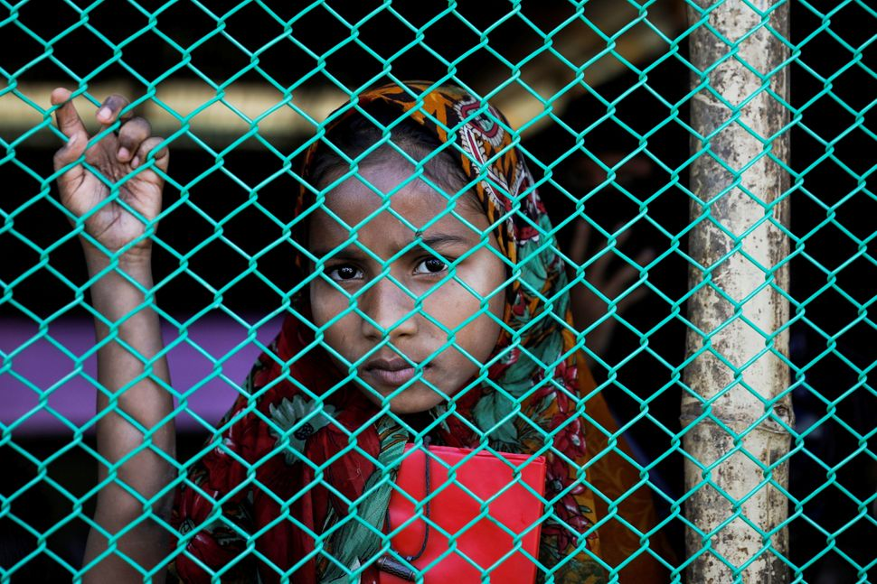 A Rohingya refugee girl looks out from a makeshift school at the Palongkhali refugee camp near Cox's Bazar, Bangladesh, on De