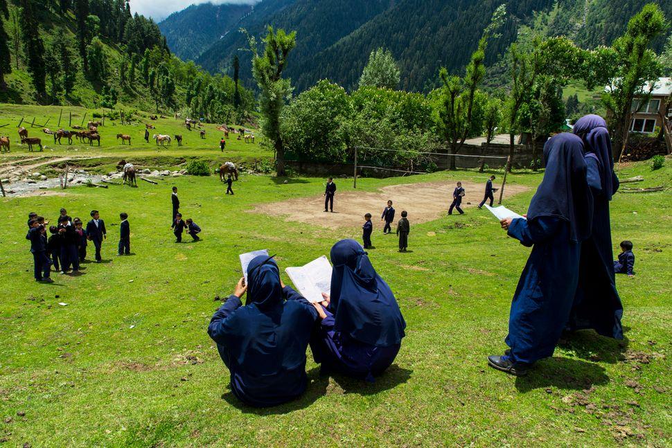 Muslim schoolgirls read outside during a break in Kashmir, India, on June 7, 2017.