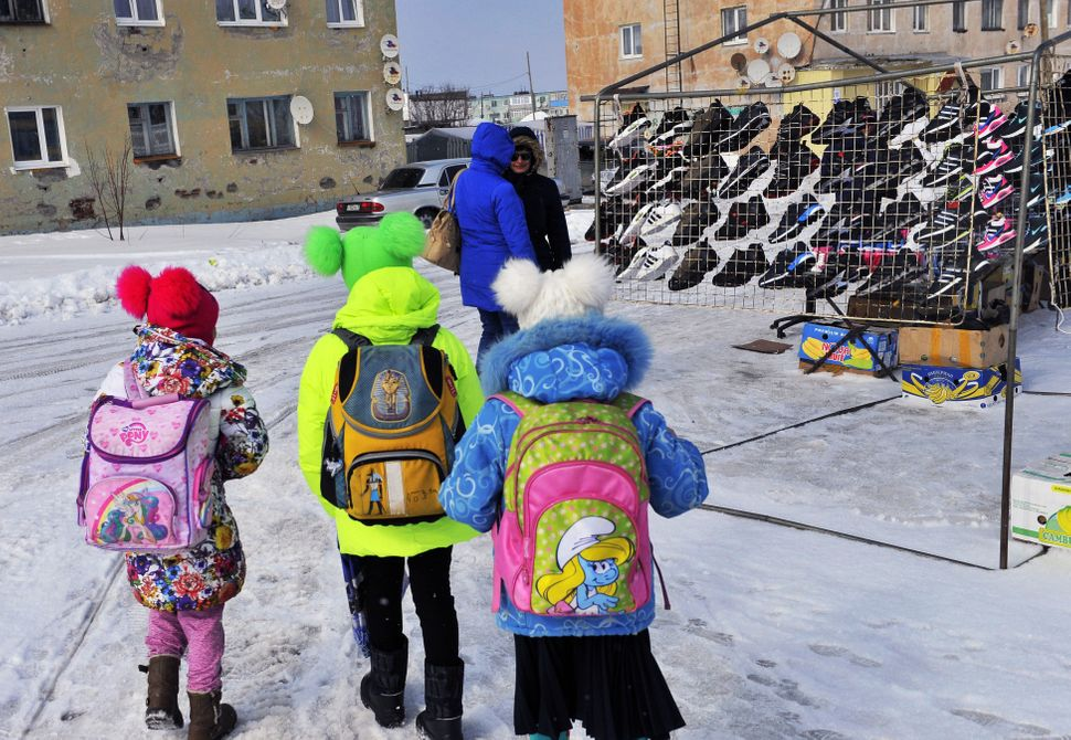 Children with schoolbags near a shoe stall in the settlement of Teriberka on the Arctic coast of north-west Russia, on April
