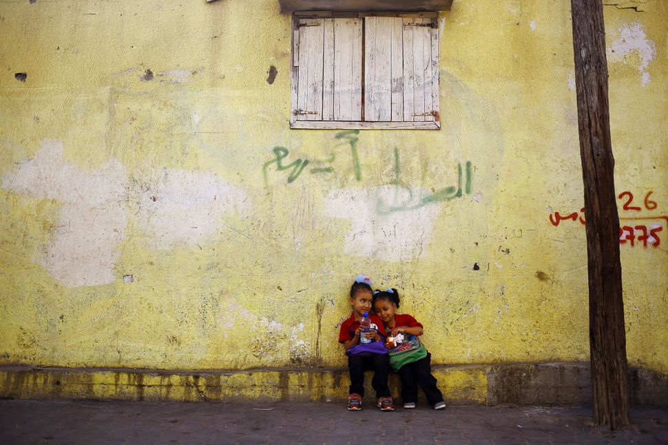 Palestinian schoolgirls wait for a bus that will take them to school outside their home in Gaza City on Sept. 7, 20