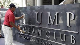 A worker removes the Trump sign letters from outside the hotel in Panama City on March 5, 2018.  The new owner of the luxury hotel Trump in Panama said that he managed to expel from the administration of the business the company linked to the president of the United States, Donald Trump, with which he has a complex lawsuit in the United States, which Panamanian prosecutors are investigating. / AFP PHOTO / STR        (Photo credit should read STR/AFP/Getty Images)