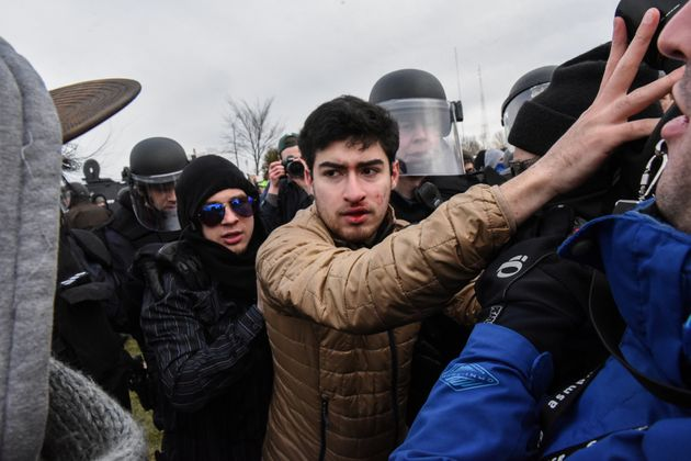 Police officers escort aman through protesters to the Richard Spencer speech on March 5,