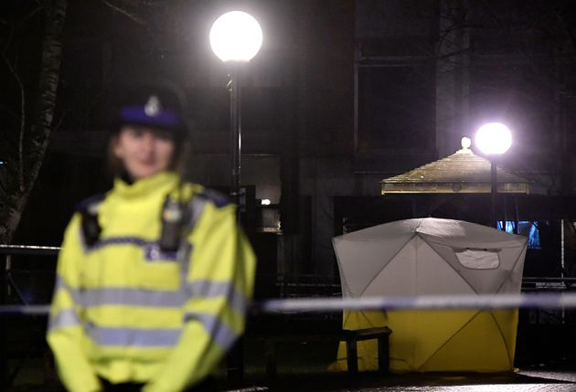 Police officers stand guard beside a cordoned-off area in