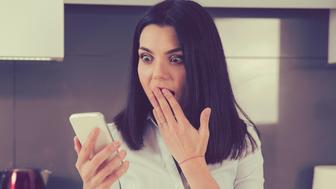 Closeup portrait shocked anxious woman looking at phone seeing bad photos message with scared emotion on face