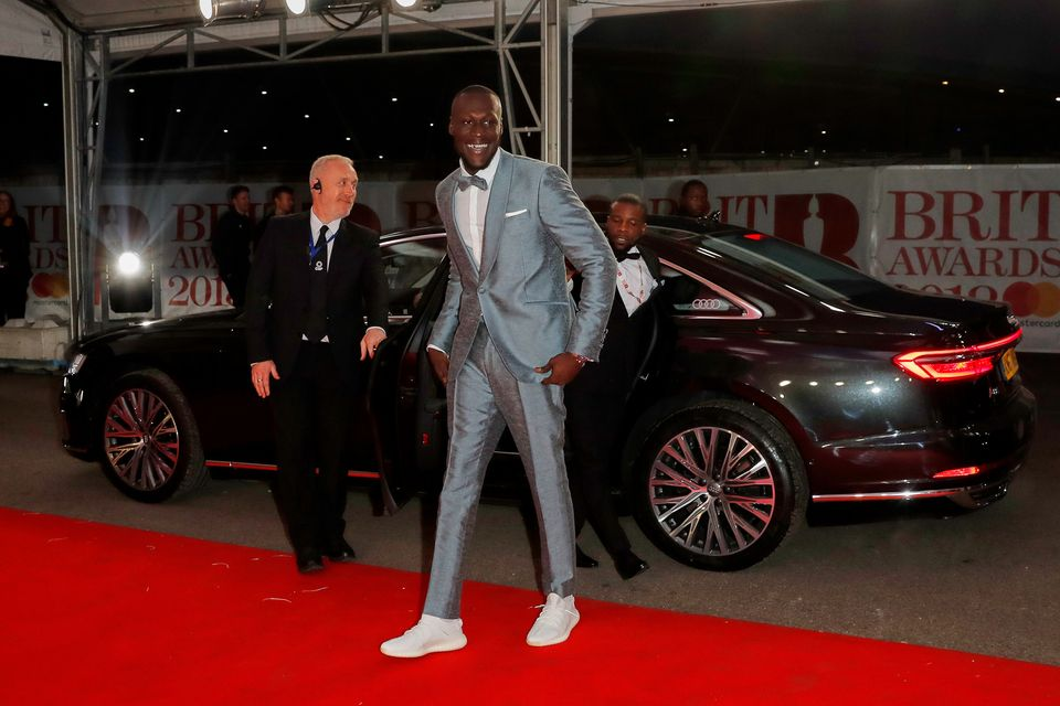 Stormzy arrives at the BRIT Awards wearing a grey suit, bow tie and white