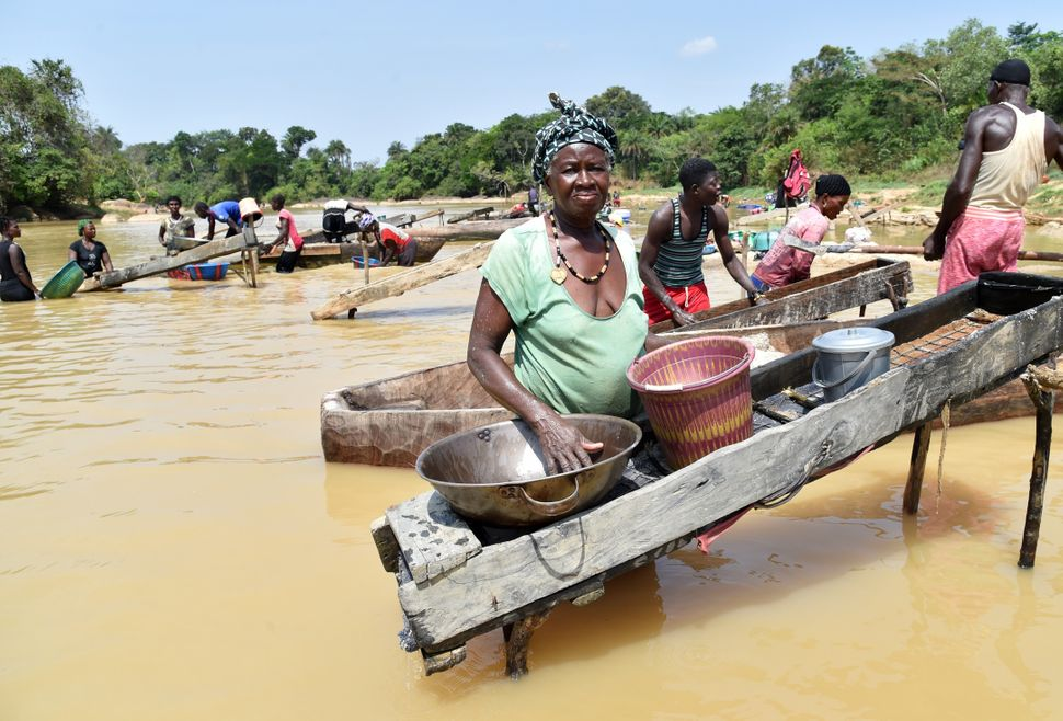Gold prospector Awa Kamara, 65, poses for a photograph in the Pampana River on March 5, 2018, near Mekeni, Sierra L