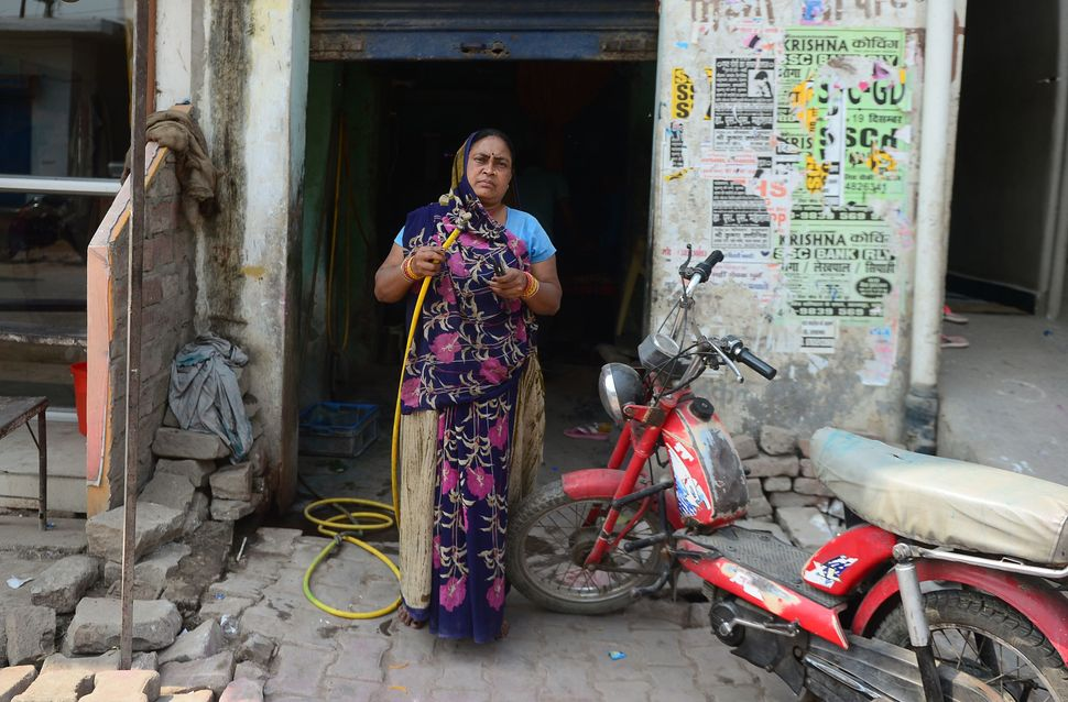 Bike mechanic Rajpati Devi, 45, poses at her roadside workshop in Allahabad, India, on Feb. 24, 2018. Devi, a mother of