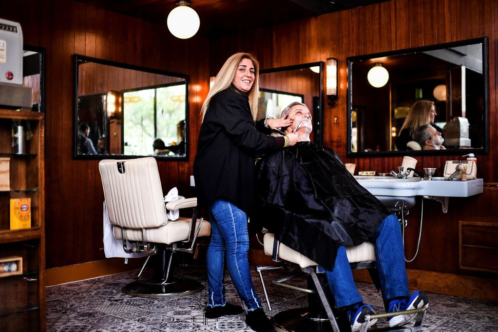 Barber Dalia Antunes, 44, poses at the Oliveira Barbershop in Lisbon, Portugal, on March 3, 2018.