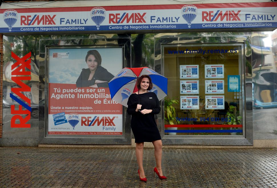 Cristina Munoz Ferraro, 37, is a real estate agentat Remax Family. Here she poses for a picture at the Remax Family off