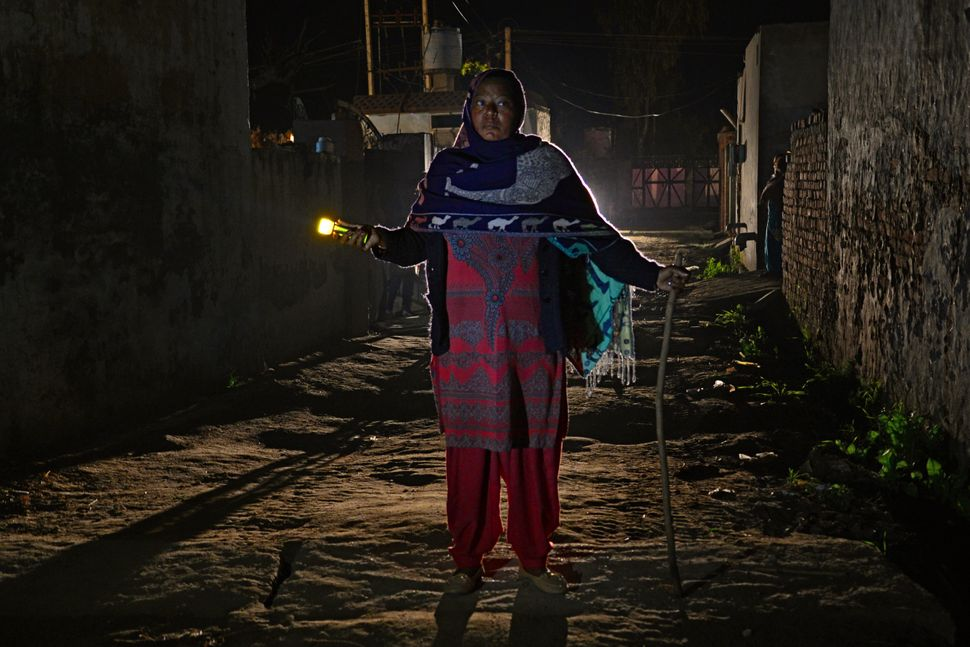 Kuldeep Kaur, 51, is an Indian watch woman for the Bhangiwal village near Mehatpur, India. Here she walks with a flashlight d