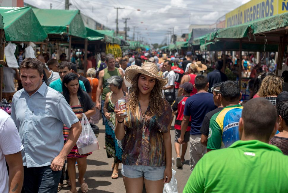 Venezuelan refugee Maria Marchan, 23, poses for a picture as she sells beers for a living at a street market in the city of B