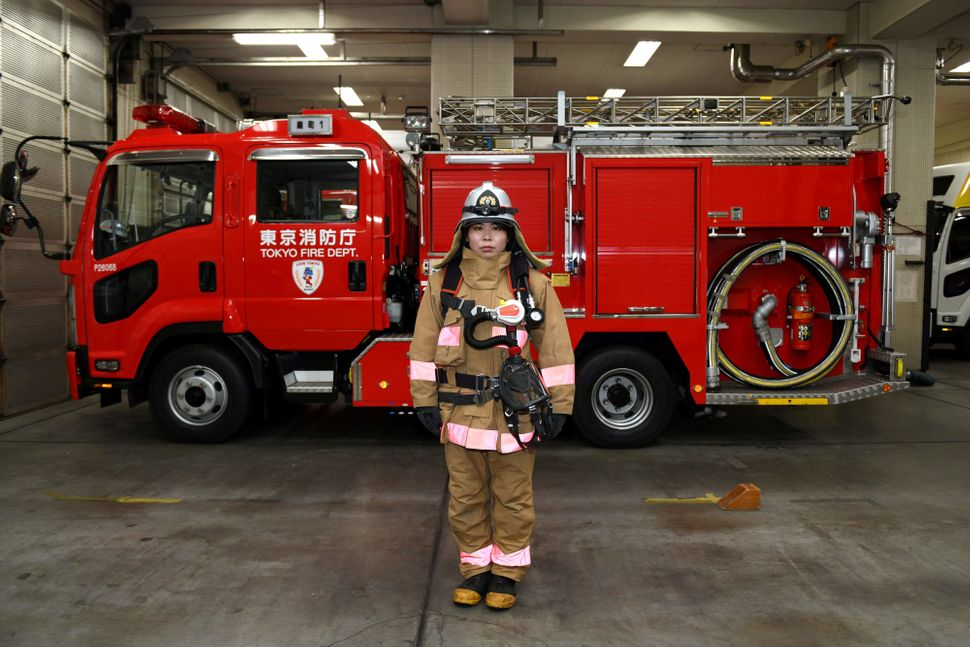 Firefighter Ran Namise, 24, poses in front of a fire engine at Kojimachi Fire Station in Tokyo on Feb. 23, 2018.