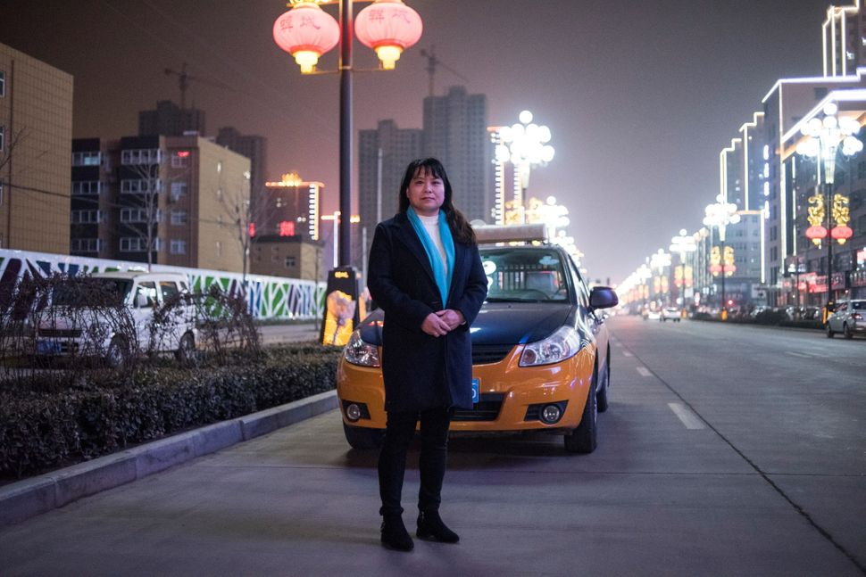 Taxi driver Yang Fengxia, 45, poses in the street in Hancheng, China, on Feb. 16, 2018.