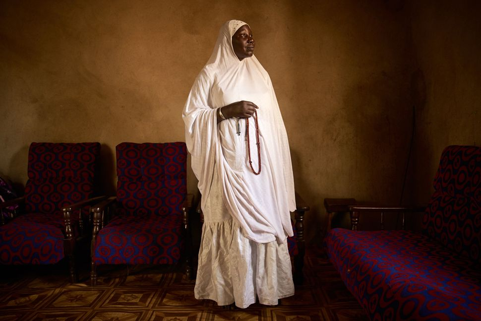 "Houssa Nientao, 64, is one of the few female Muslim monks, also known as ""marabouts,"" in Bamako, Mali. Here she poses in a ro"