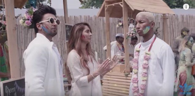 Pharrell Williams listens as Bollywood star Ranveer Singh and presenter Anusha Dandekar explain Holi, a Hindu sprin