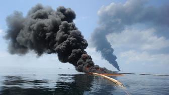 "Dark clouds of smoke and fire emerge as oil burns during a controlled fire in the Gulf of Mexico, May 6, 2010. The U.S. Coast Guard working in partnership with BP PLC, local residents, and other federal agencies conducted the ""in situ burn"" to aid in preventing the spread of oil following the April 20 explosion on Mobile Offshore Drilling Unit Deepwater Horizon. Photo taken May 6, 2010.  REUTERS/Mass Communication Specialist 2nd Class Justin Stumberg-US Navy/Handout (UNITED STATES - Tags: DISASTER ENERGY)"