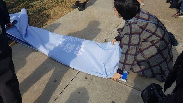 7일 서울 '연트럴파크'에서 예정됐던 정봉주 전 의원의 서울시장 출마 기자회견이 취소되자 캠프 관계자들이 펼침막을 정리하고