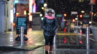 A woman walks as snow falls in Times Square in Manhattan in New York City, New York, U.S., March 7, 2018. REUTERS/Amr Alfiky