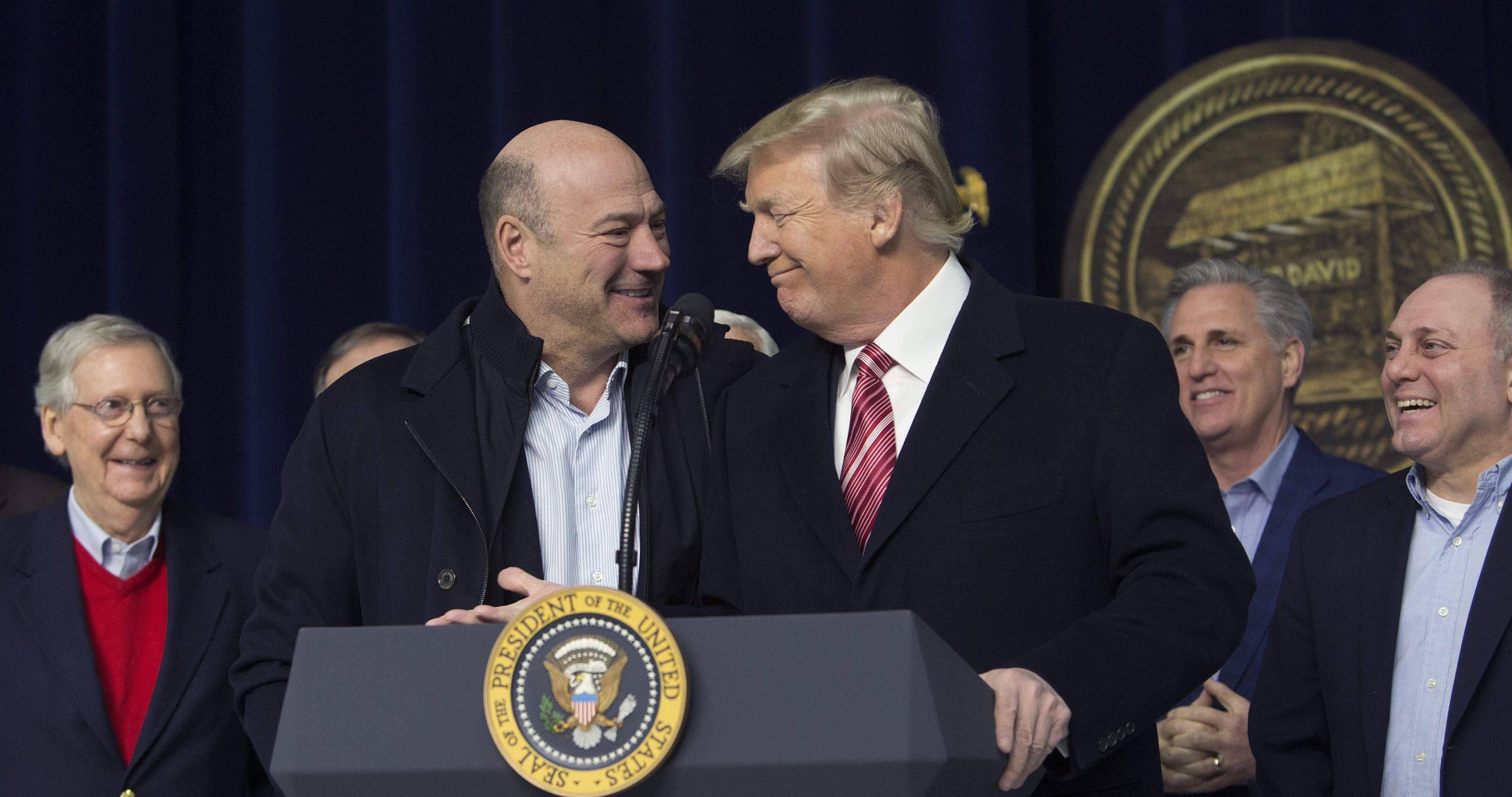 U.S. President Donald Trump, center right, and Gary Cohn, director of the U.S. National Economic Council, center left, smile during a press conference with cabinet members and Republican leadership at Camp David in Thurmont, Maryland, U.S., on Saturday, Jan. 6, 2018. Donald Trump said hes a 'very stable genius,' a day after a new book about the president's first year in the White House -- dismissed by Trump as 'fiction' -- claimed that many of his top aides and confidants consider him unfit to hold office. Photographer: Chris Kleponis/Pool via Bloomberg