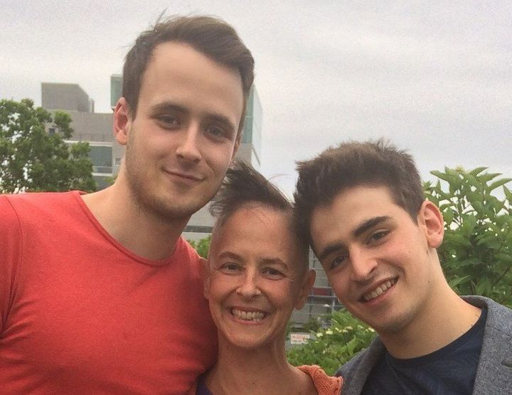 <em>S</em>usan, with her hair mostly out from chemo, and her sons Oliver (left) and Nathan (right) at Nathan's graduation from the National Circus School (background).