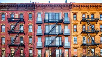 Top stories of colorful Williamsburg brownstone apartment buildings with steel fire escape stairways. Copy space in the sky above.