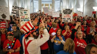 Striking school workers hold signs and chant inside the West Virginia Capitol in Charleston, West Virginia, U.S., on Friday, March 2, 2018. A week ago, thousands of public school teachers in West Virginia went out on strike, a rare but familiar union-organized action to protest low wages and rising health-care costs. Tuesday night, state union leaders and the Governor Jim Justice reached a deal, and the teachers were expected to be back at work on Thursday, but they didn't go. Unsatisfied with the resolution, they stayed on the picket line, mounting one of the country's biggest unauthorized 'wildcat' strikes in decades. Photographer: Scott Heins/Bloomberg via Getty Images