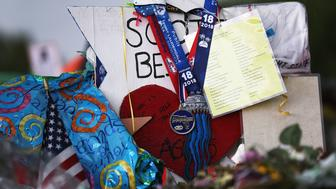 PARKLAND, FL - MARCH 07:  The state championship medals for the Marjory Stoneman Douglas High School Eagles hockey team hang from a cross at a memorial in front of the school dedicated to victims of the February 14 mass shooting on March 7, 2018 in Parkland, Florida.  The team won the champsionship 11 days after the shooting that claimed 17 lives.  (Photo by Joe Raedle/Getty Images)