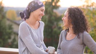 A beautiful young ethnic woman fighting cancer and wearing a head wrap shares a few minutes of cheerful and vibrant conversation with her sister. They are talking and smiling while they lean against the railing of a back deck outside.