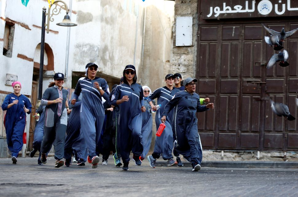 Women run during an event marking International Women's Day in Old Jeddah.