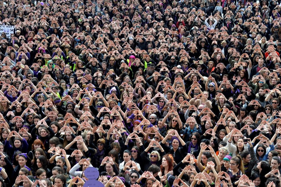 Protesters form triangles with their hands during a demonstration for women's rights.