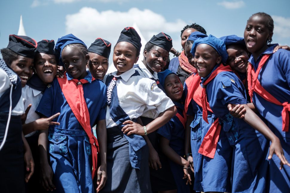 Members of Kenya Girl Guides take photos after attending a ceremony to mark International Women's Day.