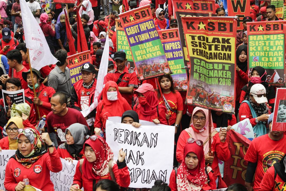Indonesians hold placards during a rally, organized by several women's organizations, to commemorate International Women's Da