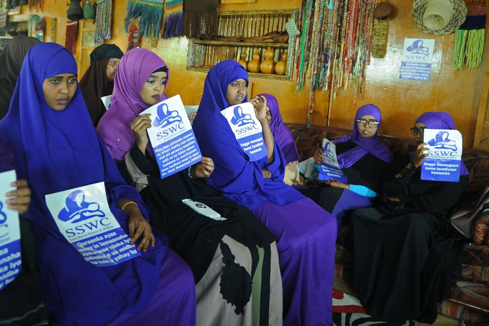 "Somali female activists, holding messages that read ""Save Somali Women and children,"" gather to mark International Women"