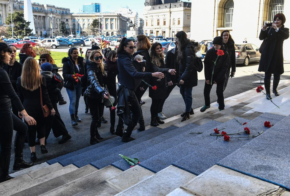 Women throw flowers on the steps of the Romanian Ministry of Interior during a protest on International Women's Day.